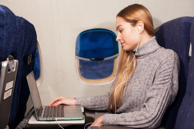 飛行機で機内WiFiを使っている女性